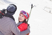 Chinese couple standing on ski slope with skis
