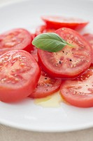 Slices of tomato with oil and basil