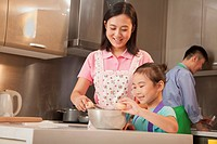 Chinese family cooking together in kitchen