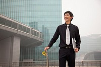 Chinese businessman holding skateboard