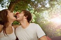 young couple having fun with cherries in garden
