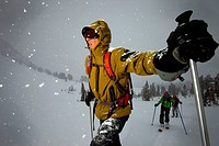 One man looking up into a storm while backcountry skiing in cool light.
