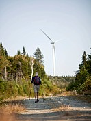 A man hikes along a trail with a wind turbine looming in the background.