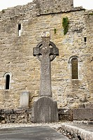 A Large Celtic Cross Monument In Front Of The Ruins Of A Stone Building, Ireland
