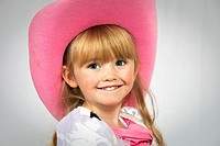 Portrait of a young girl aged 3, looking at the camera and wearing a pink cowboy hat