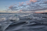 Waves of the atlantic ocean break over icebergs outside the glacial lagoon jokulsarlon, iceland