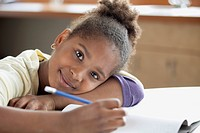 African American middle school student leaning on school desk