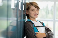 Male, middle school student leaning against school lockers.
