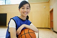 Female, middle school student posing with basketball.