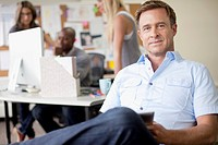 Handsome, middle_aged designer in office with pc tablet