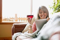 Middle_aged woman drinking wine while browsing