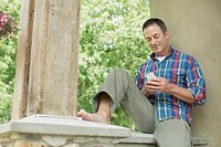 Middle-aged man texting on smart phone outdoors (thumbnail)
