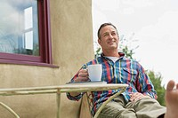 Middle_aged man relaxing with a coffee outdoors.