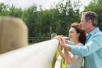Middle_aged couple standing together at corral fence