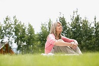 Middle_aged woman sitting outdoors in grass