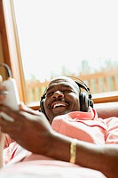 African American man lying on couch listening to music