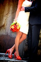 non-traditional bride & groom embracing in front of the rustic winery @ their wedding wearing orange shoes