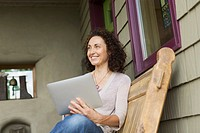 Middle_aged woman using pc tablet on outdoor porch