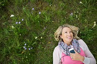 Pretty, middle_aged woman listening to music in meadow