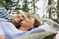 Couple relaxing in hammock together.