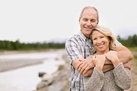 Portrait of middle_aged couple hugging by waterfront