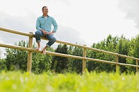 Handsome, middle_aged man sitting on corral fence.