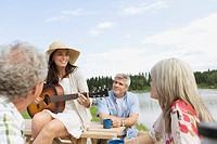 Pretty, mid_adult woman playing guitar for friends