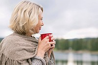 Mature woman having coffee while looking out over water