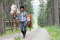 Young woman walking horse along path