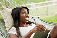 Young adult woman relaxing with book on hammock
