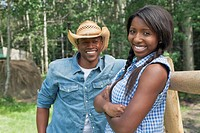 Attractive, African_American couple standing by fence on rural property
