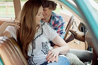 Young couple cuddling in vintage car