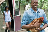 Mid_adult, African_American man holding chicken