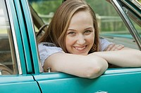 Pretty, young adult woman leaning out car window