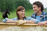 Attractive couple pausing from chores by work truck