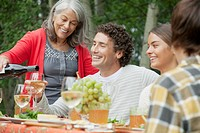 Family enjoying wine and food outdoors