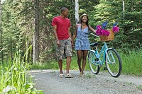 Young couple holding hands and walking bike on pathway