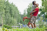 Mid_adult man hugging and lifting partner by the vegetable garden