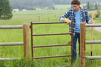 Middle_aged man opening gate to paddock on rural property