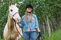 Teenage girl holding horse by reins