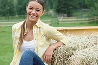 Teenage girl leaning on hay bale in back of pick_up truck