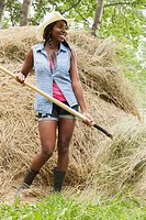 Pretty, African_American woman using pitchfork to do chores