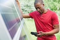 Mid_adult man checking solar panel with volt meter.