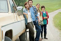 Rural family of four standing by work truck.
