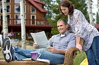Couple looking at newspaper together outside cottage