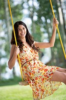 Pretty, mid-adult woman on outdoor swing (thumbnail)
