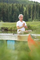 Senior man meditating in lotus position on dock