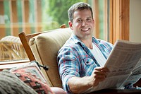 Handsome, mid-adult man reading newspaper at cottage (thumbnail)