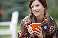 Pretty mid-adult woman warming up with coffee and afghan (thumbnail)