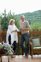 Middle-aged couple enjoying coffee together on their deck (thumbnail)